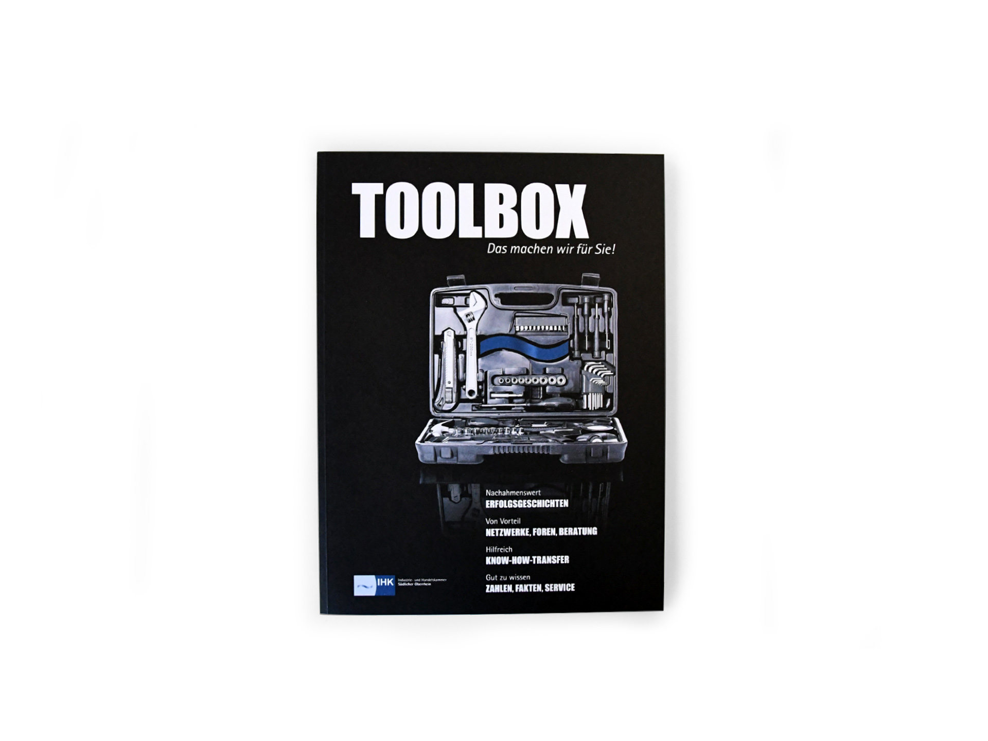 IHK Magazin TOOLBOX - Cover: Offener Werkzeugkasten mit Werkzeugen und der Welle des IHK-Logos.