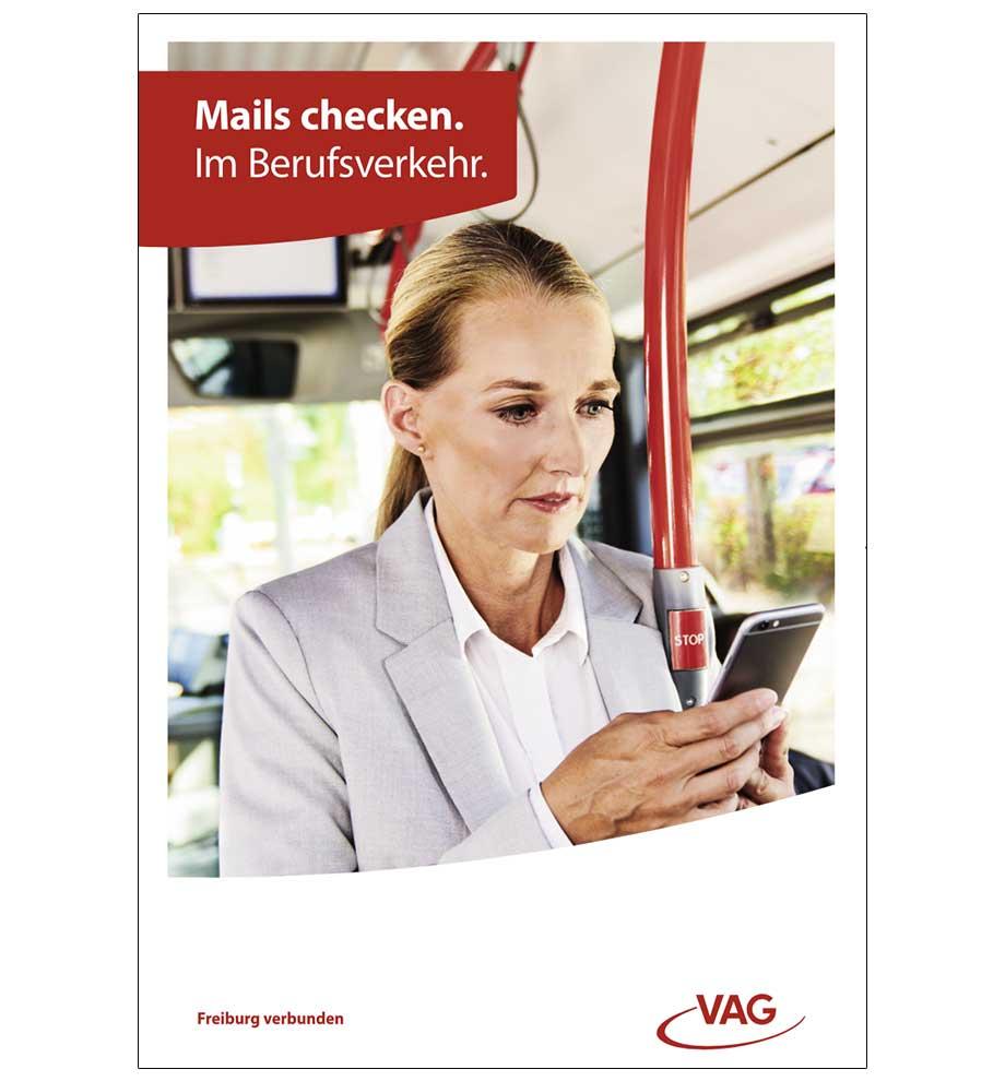 VAG Freiburg Werbung von Werbeagentur Schleiner und Partner - Business Frau steht im Bus der VAG Freiburg und checkt ihre Mails auf ihrem Smartphone. Der Titel lautet: Mails checken. Im Berufsverkehr.