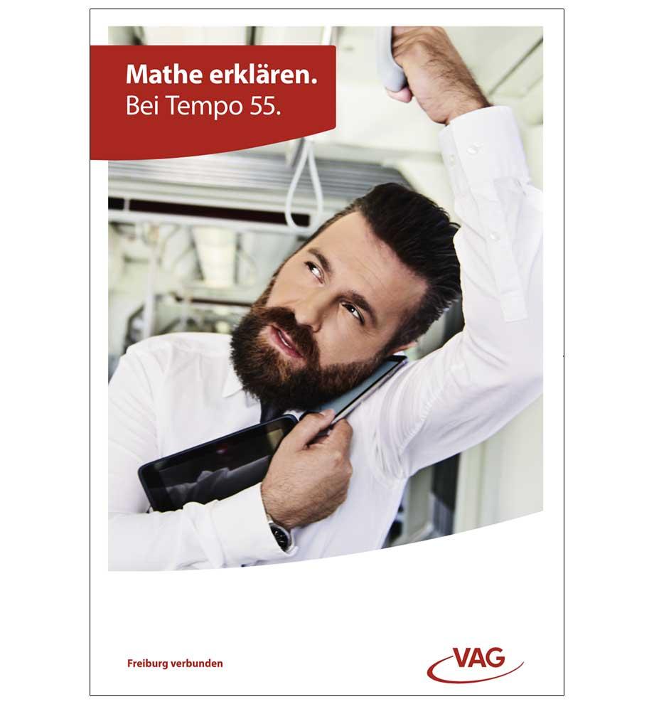 VAG Freiburg Werbung von Werbeagentur Schleiner und Partner - Business Mann steht in der Stadtbahn Freiburg, hält sich an der Deckenhalterung fest und balanciert ein iPad während er mit seinem Smartphone telefoniert. Der Titel lautet: Mathe erklären. Bei Tempo 55.