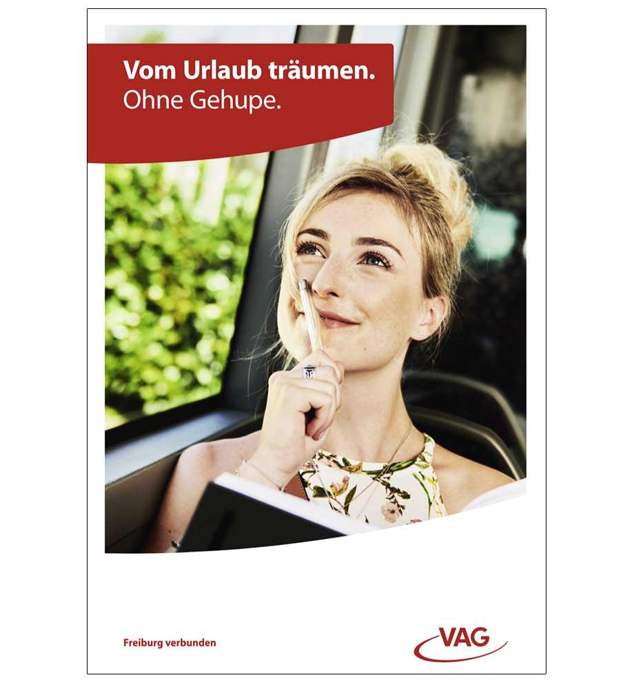 VAG Freiburg Werbung von Werbeagentur Schleiner und Partner - Junge Frau schaut träumend nach oben, hält sich einen Stift an ihren Mund und hält ein Notizbuch in der Hand. Der Titel lautet: Vom Urlaub träumen. Ohne Gehupe.